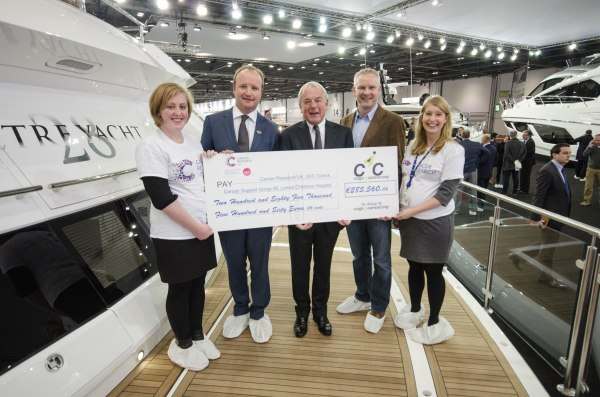 Cogs4Cancer present a cheque for €285,560.06 to Cancer Research UK at the London Boat Show. L to R - Chloe William (CRUK), Ben Young (President of C4C and MD of Sunseeker SYM), Robert Braithwaite CBE (Autumn Trust), Steve Crowe (C4C Rider and MD of Yachting Pages) & Felicity Louden (CRUK)