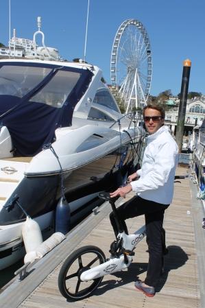 Tom Wills tests out the bike alongside a Sunseeker in Torquay marina