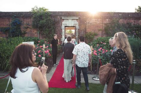 Guests walk down the red carpet entrance